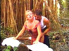 A lustful blonde chick with big fake tits gives a pleasurable blowjob in the forest. Then this hottie lifts up a dress and gets fucked in her shaved pussy.