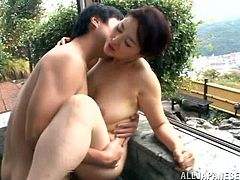 This experienced Japanese woman kisses a younger guy in the bath. Then she drops to her knees and gives a blowjob. This lucky dude fucks the woman in her shaved pussy. The guy is lucky to fuck such a hot MILF.