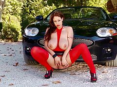 Check out this hot solo scene where the sexy redhead Eva Notty shows off her big natural tits and pink shaved pussy as she poses around a sports car.