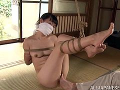 Naked Sayoko gets tied up with ropes. The guy also puts a gag in her mouth. This Asian babe gets her pussy fingered. She enjoys despite the fact that she is bounded.