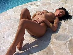 Witness this hot solo model video where a brunette babe, with big knockers wearing a sexy bikini, touches herself lying on the floor.