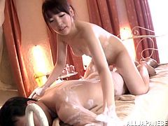 A slim Japanese girl oils a guy up and gives him an amazing massage. A guy touches Iroha's boobs with his hands and feet.