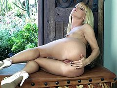 Have fun watching this blonde cougar, with natural jugs wearing a cute bra, while she touches herself sitting on a table in a really erotic way.