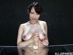 Pretty Japanese milf Nanako Mori shows her beautiful natural tits. Then she oils a dildo and begins to rub it in between her big jugs.