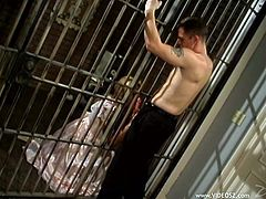 A blonde milf comes to her husband who is in prison. She kneels in front of the cell and sucks the dude's boner through the bars.