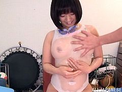Kinky Japanese skank Wakaba Onoue wearing a swimsuit lets a dude pour oil on her natural tits and cunt. The guy rubs Wakaba's snatch and then fucks it with a dildo.