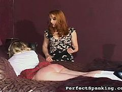 Mistress Gemini is a ruthless redhead. She punishes her blonde slave by spanking her bare ass cheeks with her palms and with a paddle. The girl is in agony.
