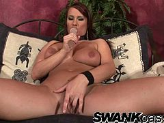 A curvaceous MILF with big natural boobs sits on a couch with her legs wide opened. She toys her tight pussy and fondles it.