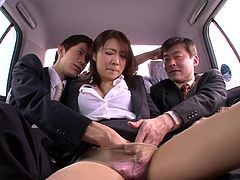 A horny Japanese bitch is having fun with two dudes in a car. She lets them play with her pussy, then shows her cock-sucking skills to the guys.