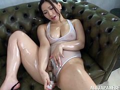 Have a good time watching this brunette cougar, with gigantic boobs wearing a sexy bathing suit, while she touches herself covered in oil.