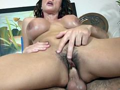 Check this brunette cougar, with a nice ass wearing a black bra, while she goes hardcore with a horny dude over a couch in a reality video.