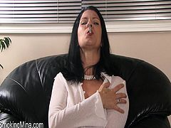 A sizzling big-breasted brunette mom is giving an interview indoors. She tells about herself and smokes a cigarette.