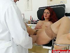 This busty redhead has her boobs measured by her gynecologist and her pussy examined with a speculum. She listens to his instructions carefully and obliges.