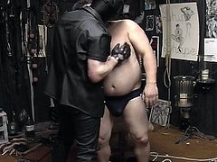 Watch this masked gay master untie his fat slave so he can stuff his cock into his slave's fat mouth in this gay bdsm free tube video.
