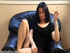 Marvelous brunette in black top with cigar fetish smoking heavily on a black sofa indoors displaying her sexy thighs in a closeup shoot