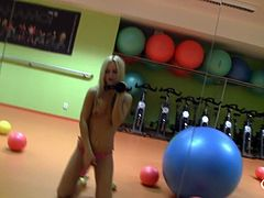 Sabrina is all alone by herself in the gym and she is ready to have some fun. She bounces up and down on the exercise balls and this makes her so happy. She films her self as she strokes her pink stra on in the mirror.