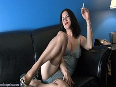 Salacious mature brunette called Mina, wearing a corset and panties, is smoking a cigarette in the living room. She rubs her natural boobs ardently, then spreads her legs wide apart and plays with her cunt.