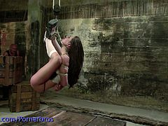 This dirty whore is tied up and suspended in the air in a dungeon. Her master fucks her face hard and deep.