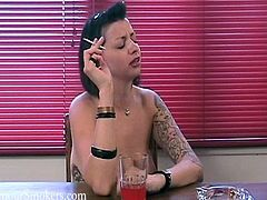 Tattooed brunette mom Violet S is sitting at the table and smoking a cigarette. She flashes her big natural tits and tells about herself.