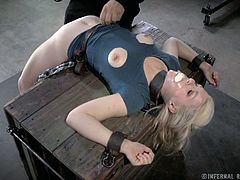 This unlucky slave is in for some serious pain. She is strapped to the wooden block and bent over backwards. You can her her back crack as she is bent over in a painful way. Her nips are poking through holes in her swimsuit, but her master cuts off her top and pours hot wax all over her boobs.