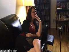 Kinky brunette mom, wearing glasses, is having fun indoors. She tells about herself, smokes a cigarette seductively and then lifts her legs and flashes her butt.