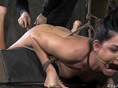 Naked and tied hard, India begins to have a pretty clear idea of what will happen to her. Her mouth is kept opened with a bondage device and a dildo is slide between those lips before the executor begins to have some fun with her. He dripped hot wax on her ass but now he's really punishing her butt!