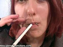 A gorgeous redhead with long hair, beautiful natural tits and a shaved pussy enjoys touching her awesome body while smoking.