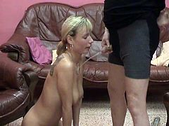 Kinky blonde mom kneels in front of a guy and gives him a blowjob. Then she lets the dude pee on her tits. After that she squats and fills a glass with her piss.