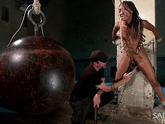 The ebony slave is tied up to a pillar in a construction site. The master has put painful clips all over her body. He presses a vibrator against her vagina very firmly and the slut moans due to the pain and pleasure.