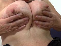 This dirty slut juggles her saggy boobs and then spreads her legs wide open to reveal her old pussy. She can even lick her own nipples. She sticks her fingers in her pussy hole. Doesn't she look good dressed up in her stockings and lingerie.