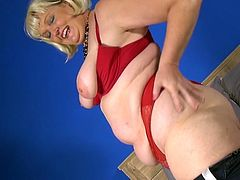 This blonde fatty has been around the block a few times. The mature slut is wearing nothing but red lingerie. She shows off her celluloid covered butt cheeks and juggles her saggy tits before laying back and masturbating with a dildo.