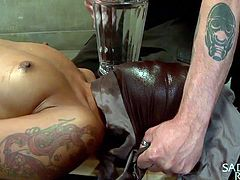This ebony slave is upside down and her master is fingering her cunt while he uses a hitachi vibrator on her clit. He ties her to a board and places a rag over top of her face. She has cold water poured down onto her face.