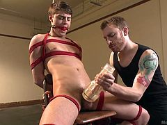 Take a look at this gay slave. He is tied up in rope to the chair and has a fleshlight used on his rock hard cock. One of the masters grabs the slaves cock and tug him off to get him hard. The slave is gagged so he can't yell out as the master play with his sensitive cock.