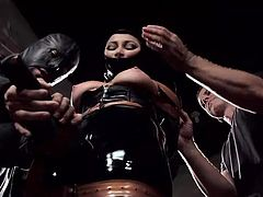 Dani is covered in latex; her face is nearly completely encased within the latex mask. One of the masters uses a torture device on her nipples. The powerful dominators slaps her big breasts and teach her how to have the best orgasm. She sits on the sybian; one of the masters controls the intensity.