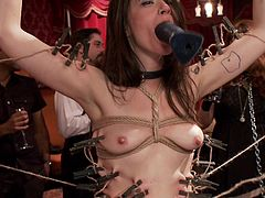 At this sex party the slave is made to serve the guest snacks. But she has something else in mind. The master has clamps on her nipples and rope tightly wrapped around her body. She gets a dildo shoved in her mouth and then, a thick cock in her mouth.