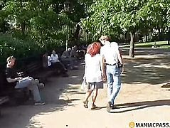 A chap in a park giving a kiss crumbs
