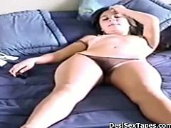 This Indian chick sits in bed with her panties on. She records herself with a webcam that she controls through a remote control. She focuses on her nipples before squeezing them hard.