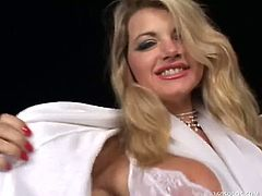 Gorgeous blonde MILF Vicky Vette smiles for the camera in her white housecoat. She undoes it to show off the sexy white lingerie she has on underneath. She frees her large tits from her bra, and she turns to show off her fine ass in her thong underwear. She sits back in a chair and undoes her garter belt before sensually sliding off her white stockings. She sucks on a glass dildo, getting it nice and wet before she uses it to fuck her tight pussy. She rubs a red vibrator against her erect clit, and she slides the glass dildo up her tight ass. She gets off knowing you're watching.