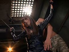 A slutty Japanese with brown long hair has been captured and isolated down in the basement. She cannot escape, as her hands are tied up from the ceiling. Her body looks amazing in that kinky molded black leather costume. Click to see the guy using a vibrator.