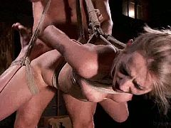 This blonde girl is beautifully bound with her legs spread and her hands behind her back. She is hanging from the ceiling while her master fucks her pussy.