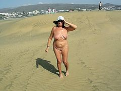 Beautiful old whore walks in the dunes