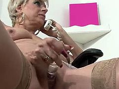 Dimonte is a busty blonde woman. She is British and mature, but this doesn't stop her from masturbating at work. She sucks on a glass dildo and fucks herself.