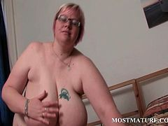 Blonde mature BBW in glasses licking her giant boobs in bed