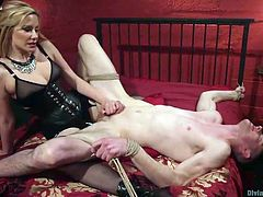 Maitresse Madeline has her slave exactly where she wants him. The slave is tightly bound in rope and the mistress shoves her strap on down his throat, to get it nice and lubed up with his spit. She rams the plastic cock deep into his asshole.