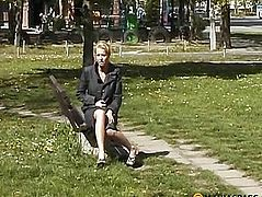 The girl sitting on a bench touching her breast