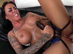 Tattooed brunette pegging her stud with a strap on dildo before riding a cock