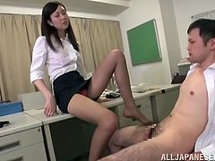 Tall Japanese office domme pleasures his cock with her feet