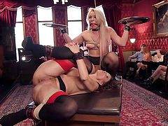 Slutty Syren de Mer is eager to spread her legs widely for a horny partner, who has bonded her awfully and put her hands in shackles. Click to watch this hot bitch pounded hard, while a blonde wearing a kinky ball gag, watches the sexy scene!