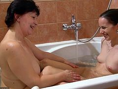 A mature lesbian feels very excited, when an attractive younger lady joins her in the bath tub. Click to watch the slutty brunette with small tits, massaging Karla's back and touching her boobs. See them using a kinky dildo for more pleasure...