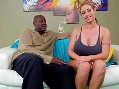 Sexy blonde gets cozy with her black hubby on their couch in front of the camera